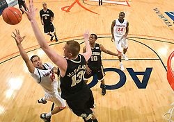 Wake Forest center Chas McFarland (13) blocks a shot by Virginia guard Sylven Landesberg (15).  The Virginia Cavaliers fell to the #13 ranked Wake Forest Demon Deacons 70-60 at the John Paul Jones Arena on the Grounds of the University of Virginia in Charlottesville, VA on February 28, 2009.