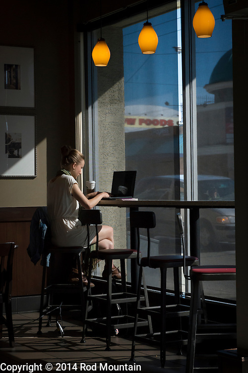The afternoon sun illuminates a young woman as she works on her laptop. Vancouver, BC © Rod Mountain