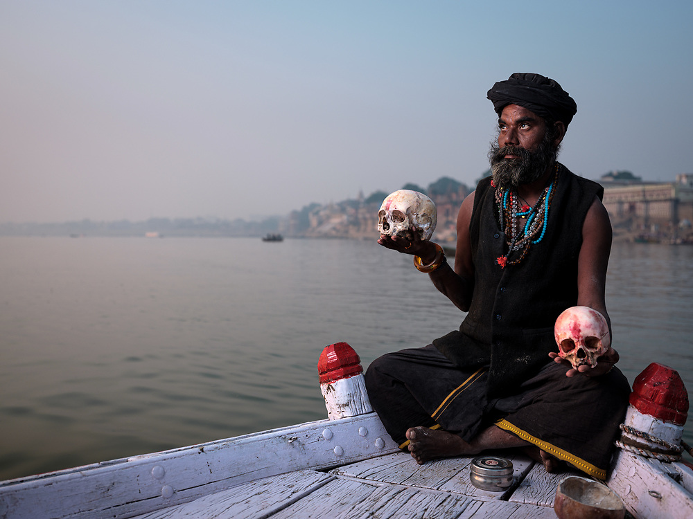 Varanasi, INDIA - CIRCA NOVEMBER 2018: Portrait of a Aghori with skull in Varanasi. The Aghoris are a small group of ascetic Shaiva sadhus. They engage in post-mortem rituals. Varanasi is the spiritual capital of India, the holiest of the seven sacred cities and with that one the most frequented places for Sadhus.