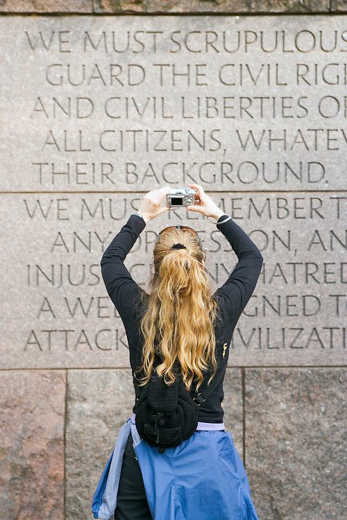Woman photographing engraved quotation Franklin Delano Roosevelt memorial Washington DC USA&#xA;<br />