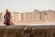 Young woman sat on balaustrade in San Sebastian (Spain)