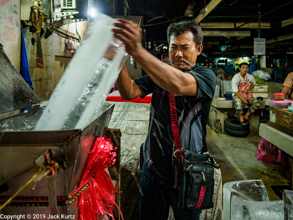 27 FEBRUARY 2019 - BANGKOK, THAILAND: A man who provides crushed ice to street venders in Bangkok's Chinatown crushes a block of ice. Bangkok, a city of about 14 million, is famous for its raucous nightlife. But Bangkok's real nightlife is seen in its markets and street stalls, many of which are open through the night.        PHOTO BY JACK KURTZ