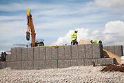 Repair work on steel mesh cages known as gabions which provide coastal defence at Chiswell, Isle of Portland, Dorset, England, UK