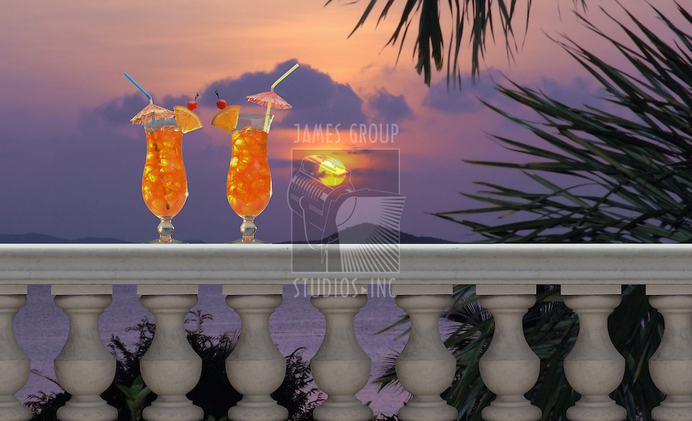 Two tropical drinks on a balcony with a tropical sunset in the background