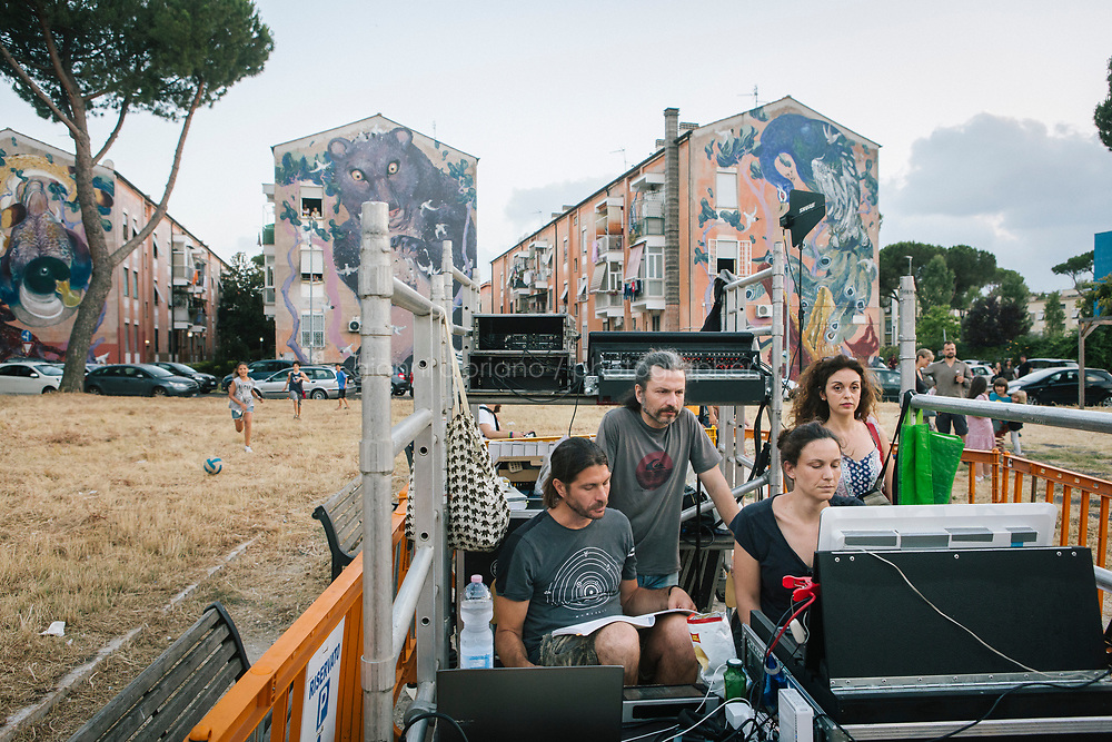 ROME, ITALY - 27 JUNE 2017: Technicians and assistants are here at work during a rehearsal of the &quot;Don Giovanni OperaCamion&quot;, an open-air opera performed on a truck in San Basilio, a suburb in Rome, Italy, on June 27th 2017.<br /> <br /> Director Fabio Cherstich&rsquo;s idae of an &ldquo;opera truck&rdquo; was conceived as a way of bringing the musical theatre to a new, mixed, non elitist public, and have it perceived as a moment of cultural sharing, intelligent entertainment and no longer as an inaccessible and costly event. The truck becomes a stage that goes from square to square with its orchestra and its company of singers in Rome. <br /> <br /> &ldquo;Don Giovanni Opera Camion&rdquo;, after &ldquo;Don Giovanni&rdquo; by Wolfgang Amadeus Mozart is a new production by the Teatro dell&rsquo;Opera di Roma, conceived and directed by Fabio Cherstich. Set, videos and costumes by Gianluigi Toccafondo. The Youth Orchestra of the Teatro dell&rsquo;Opera di Roma is conducted by Carlo Donadio.