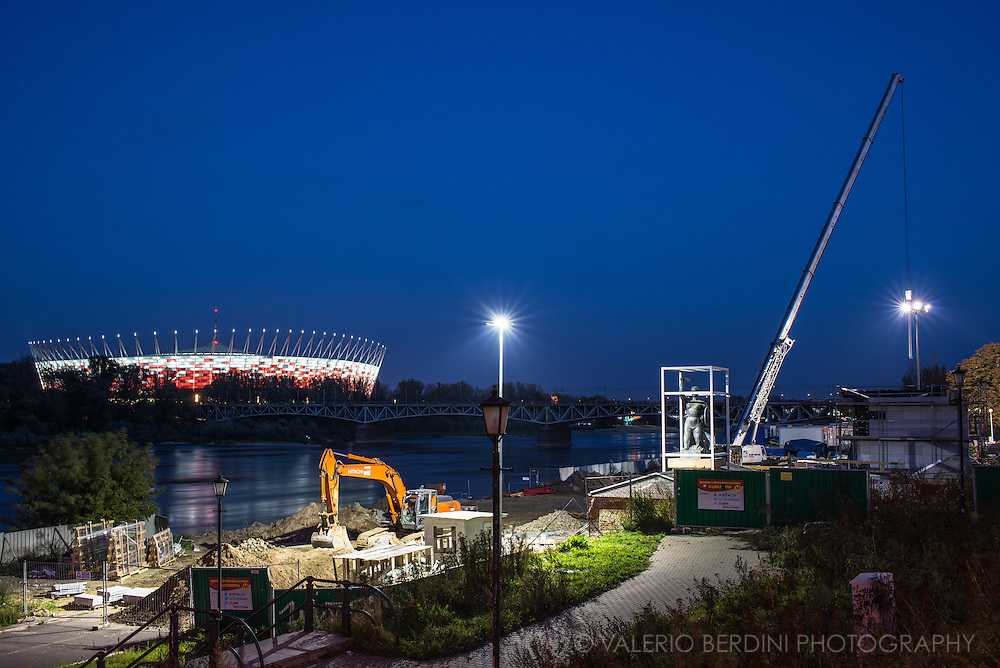 Night cityscape of River Vistula and the National Stadium. The largest stadium in Poland. It has retractable roof and its façade refers to the Polish national colors, resembling a waving Flag of Poland. On this bank works in progress and a bronze statue waiting to be installed.