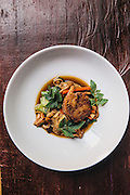 Pork shank curry with chantarelles and winter melon,<br /> crispy breast and basil at Cuisine Wat Damnak, Siem Reap