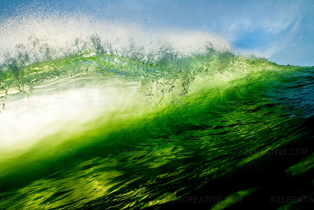 Water shot of a backlit breaking wave.