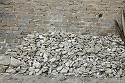 stack loose stones against an old stone wall