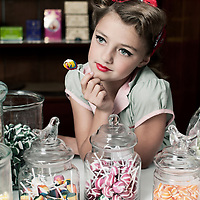 Young girl, thinking while eating a lollipop, leaning on a table with glass jars filled with candy. She is wearing red lipstick and a pretty red bow. Looking vintage, 1950's.