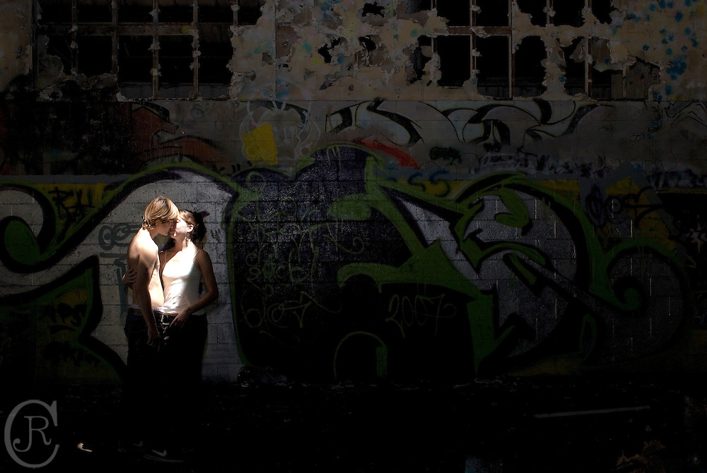 Brian Florer and Caitlyn Peterson kiss each other under a beam of light falling through an abandoned building in Ventura, Calif., on August 11, 2008. (Photography by Joseph R Cisneros II)