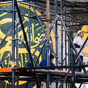 Workers renovate sections of the interior of Hagia Sophia. In the background is one of the massive calligraphy medallions on the wall. With such an old building, renovations are almost constant. Originally built as a Christian cathedral, then converted to a Muslim mosque in the 15th century, and now a museum (since 1935), the Hagia Sophia is one of the oldest and grandest buildings in Istanbul. For a thousand years, it was the largest cathedral in the world and is regarded as the crowning achievement of Byzantine architecture.