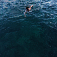 A man swims in the Mediterranean sea along the Beirut coast.