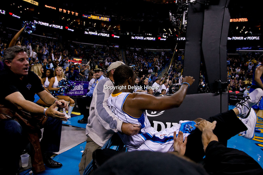 November 17, 2010; New Orleans, LA, USA; New Orleans Hornets point guard Chris Paul (3) is knocked into photographers after a score during the second half against the Dallas Mavericks at the New Orleans Arena. The Hornets defeated the Mavericks 99-97. Mandatory Credit: Derick E. Hingle