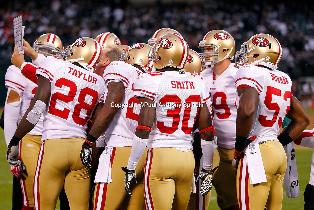 San Francisco 49ers defenders look at a play sheet during the NFL preseason week 3 football game against the Oakland Raiders on Saturday, August 28, 2010 in Oakland, California. The 49ers won the game 28-24. (©Paul Anthony Spinelli)