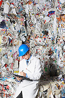 Worker holding clipboard sitting on stacks of recycled paper portrait