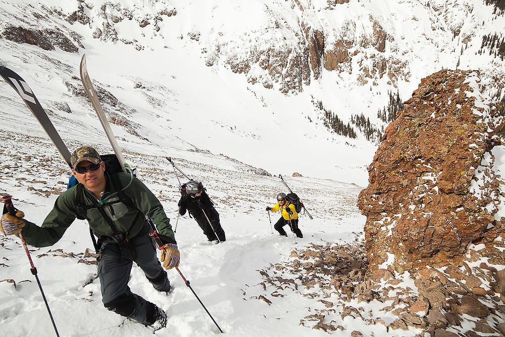 Backcountry skiers ascend the loose talus slopes of Hayden Peak, San Juan Mountains, Colorado.
