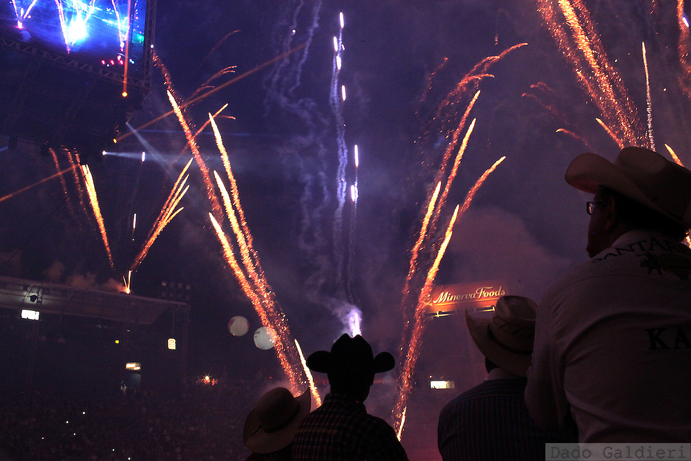 Cowboys look on as fireworks explode during the beginning of a  rodeo competition in Barretos during the Barretos Rodeo Fair in  Sao Paulo state, Brazil, Thursday, Aug. 23, 2012. Brazil is on a quick path to become a global power. Rising economy, big infrastructure projects, an emerging and eager consuming middle class and the booming national industry are the evidences and consequences of the wealth in the southern nation. But the often hidden source of all this wealth falls far from the luring Rio beaches or the Kolkata-New York mix that Sao Paulo is. Behind texan hats and a similar attitude the countrymen display their power through a myriad of projects, festivals and behavior visually analyzed here.