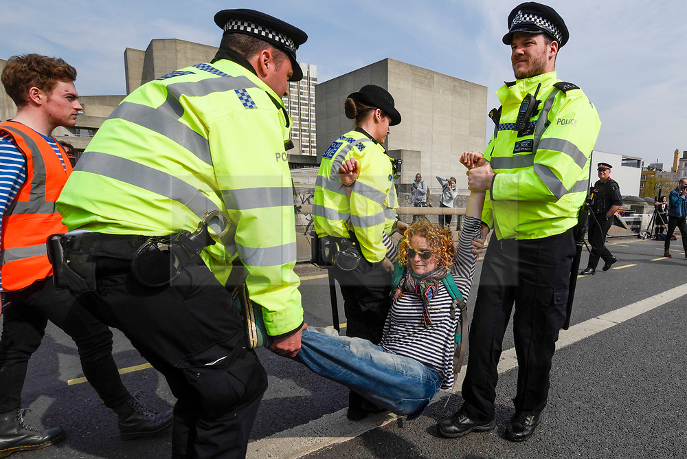 "© Licensed to London News Pictures. 18/04/2019. LONDON, UK.  Police arrest a protester on Waterloo Bridge during ""London: International Rebellion"", on day four of a protest organised by Extinction Rebellion.  Protesters are demanding that governments take action against climate change.  Marble Arch, Oxford Circus, Piccadilly Circus, Waterloo Bridge and Parliament Square have been blocked by activists in the last three days.  Police have issued a section 14 order requiring protesters to convene at Marble Arch only so that the protest can continue.  Photo credit: Stephen Chung/LNP"