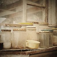 Old dusty jars on window sill.