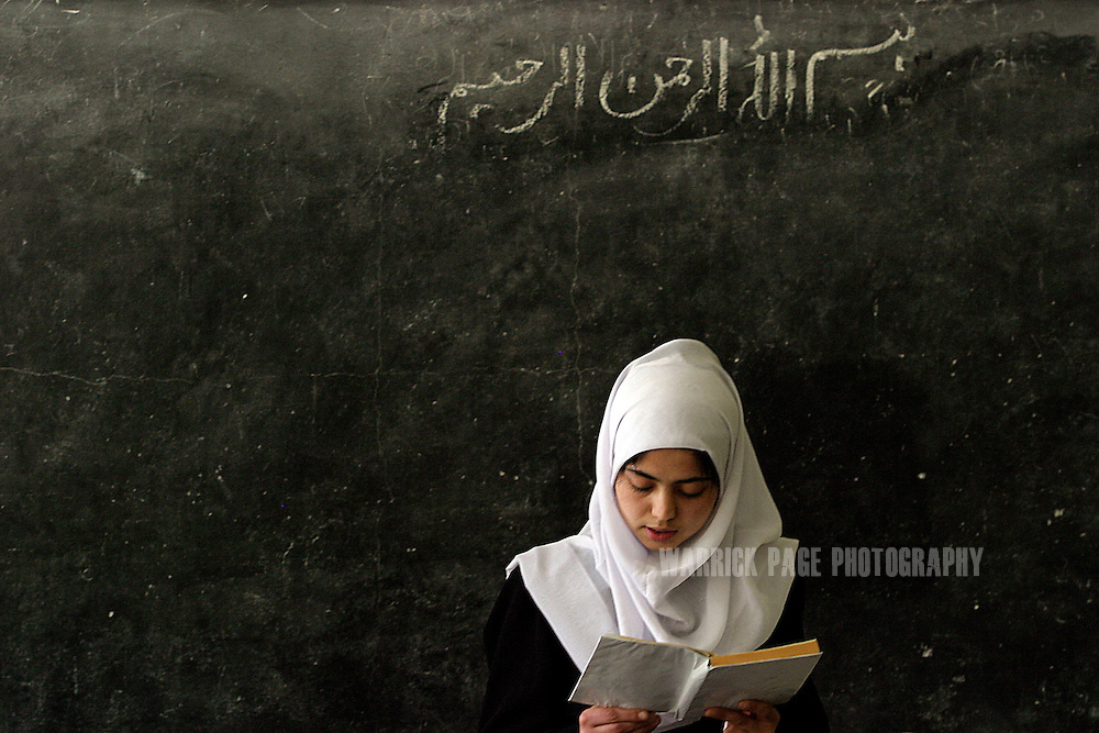 KABUL, AFGHANISTAN - APRIL 23: A student stands in front of the class and reads from a text book at Lycee Mary-Ann High School in Kabul, Afghanistan Sunday, April 23, 2006. The school is extremely overcrowded and under resourced for the 8000 students who attend in shifts between the hours of 6.30am-4.30pm. Students are desperate for more materials and extra classrooms and staff are grossly overworked due to the volume of students.  (Photo by Warrick Page)