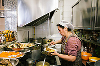 NAPLES, ITALY - APRIL 10th 2018: Owner Marianna Sorrentino prepares pennette with Genovese sauce in the kitchen of the Trattoria Malinconico, a popular restaurant in the Vomero district in Naples, Italy, on April 10th 2018.<br /> <br /> Trattoria Malinconico was opened in 1953 by current owner Marianna Sorrentino's parents-in-law. At first it was only a bulk wine cellar, but then he began making a few cooked dishes – small plates that were popular with locals, which eventually morphed into larger meals. Still today the trattoria is frequented the neighborhood's older residents, many of whom have been loyal regulars for years, as well as younger locals and workers, who often stop by for a glass of wine. The menu varies from day to day, and is typically based on traditional Neapolitan recipes. Though some dishes, like meatballs, sausages, and friarielli (rapini, a type of broccoli typical to Naples), are always available.<br />  <br /> <br /> Genovese sauce is a rich, onion-based pasta sauce from the region of Campania, Italy. Likely introduced to Naples from the northern Italian city of Genoa during the Renaissance, it has since become famous in Campania and forgotten elsewhere.<br /> Genovese sauce is prepared by sautéing either beef, veal or pork in a large number of onions, for at least two but as many as ten hours. Large, cylindrical pasta like rigatoni, ziti or candele are favored because they can hold the rich sauce.