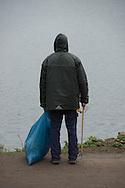 Männer mit Mülltüten streifen über den Stadpark, sammeln alte Flaschen, Papier und sonstigen Unrat ein.