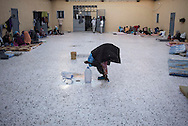 Libya, Garabulli: At Alguaiha detention center a Somali migrant captured at the sea as she was attempting to reach Italy empties bottles of not drinkable water in the courtyard of the facility on May 12, 2015. Alessio Romenzi