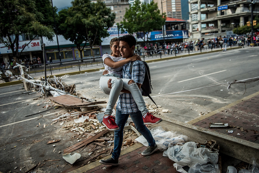 CARACAS, VENEZUELA - JULY 27, 2017: A man carries a woman over a barricade on a road blocked by protesters, in support of a national strike, called by the political opposition to last for  48 hours, all day July 26th and 27th. They called for their supporters to close businesses, not go to work, and instead create barricades to block off their streets.  Opposition controlled areas of the country were completely shut down.  The strike was called as part of the opposition's civil resistance movement - that began on April 1st, to protest against the Socialist government's attempt to elect a new constituent assembly that will have the power to re-write the constitution, and will threaten democracy.  PHOTO: Meridith Kohut for The New York Times
