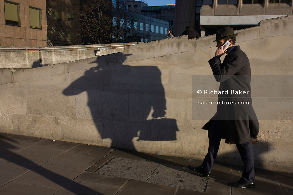 A man carrying a briefcase walks on the south side of London Bridge in Southwark, central London