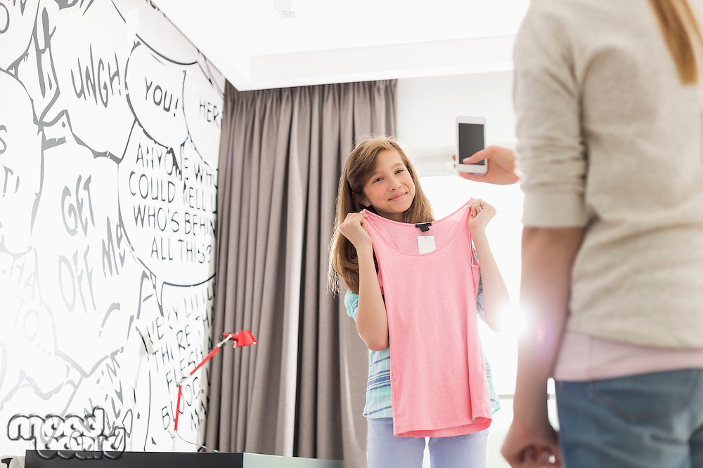 Girl trying on clothes while sister photographing her at home