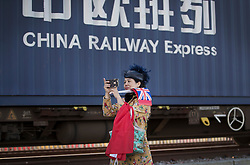 © Licensed to London News Pictures. 18/01/2017. London, UK. A Chinese woman carrying a Union Flag photographs the first direct rail freight train from China as it arrives at Barking Rail Freight Terminal east of London. The new service set off from China on the 3rd of January this year. London is now the 15th European city to join what the Chinese government calls the New Silk Route. Photo credit: Peter Macdiarmid/LNP