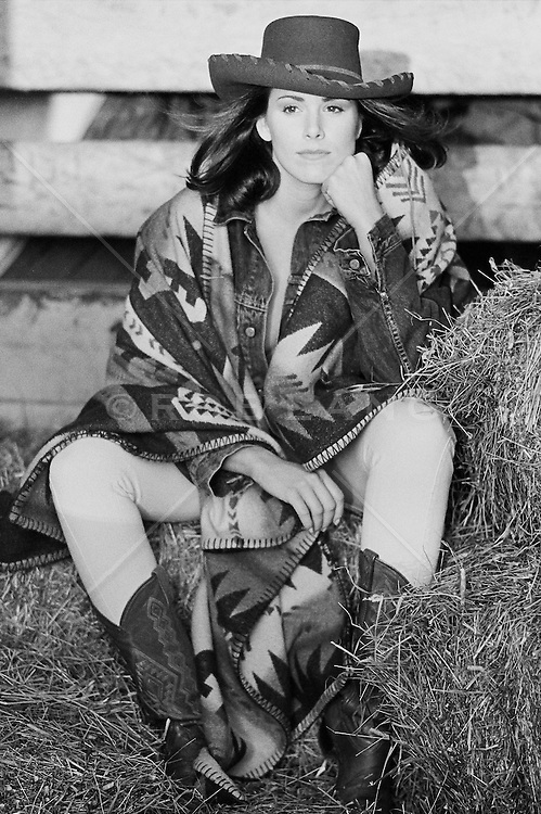 woman seated on hay bales in a barn