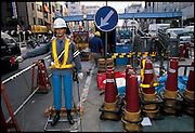 "With government-funded construction clogging roadways throughout Japan, traffic robots like this one have become increasingly common. Standing in the Tokyo restaurant supply district, this artificial policeman politely raises and lowers its arm to slow down approaching vehicles. Anzen Taro (Safety Sam), are full 3-D mock-ups of policemen so realistic that oncoming drivers can't tell them from the real thing. Although the makers of these machines describe their products as ""robots,"" many engineers would not, because they do not respond to their environment and cannot be reprogrammed. Japan. From the book Robo sapiens: Evolution of a New Species, page 170-171."