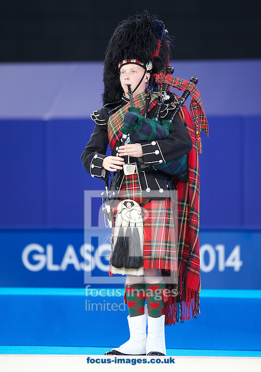 The piper before the medal presentation in the Rhythmic Gymnastics Hoops final at SSE Hydro, Glasgow<br /> Picture by Alan Stanford/Focus Images Ltd +44 7915 056117<br /> 26/07/2014
