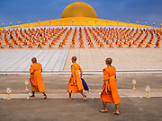 "14 FEBRUARY 2014 - KHLONG LUANG, PATHUM THANI, THAILAND:  Monks file into the main prayer area at Wat Phra Dhammakaya for Makha Bucha Day. The aims of Makha Bucha Day are: not to commit any kind of sins, do only good and purify one's mind. It is a public holiday in Cambodia, Laos, Myanmar and Thailand. Many people go to the temple to perform merit-making activities on Makha Bucha Day. The day marks four important events in Buddhism, which happened nine months after the Enlightenment of the Buddha in northern India; 1,250 disciples came to see the Buddha that evening without being summoned, all of them were Arhantas, Enlightened Ones, and all were ordained by the Buddha himself. The Buddha gave those Arhantas the principles of Buddhism, called ""The ovadhapatimokha"". Those principles are:  1) To cease from all evil, 2) To do what is good, 3) To cleanse one's mind. The Buddha delivered an important sermon on that day which laid down the principles of the Buddhist teachings. In Thailand, this teaching has been dubbed the ""Heart of Buddhism."" Wat Phra Dhammakaya is the center of the Dhammakaya Movement, a Buddhist sect founded in the 1970s and led by Phra Dhammachayo.    PHOTO BY JACK KURTZ"