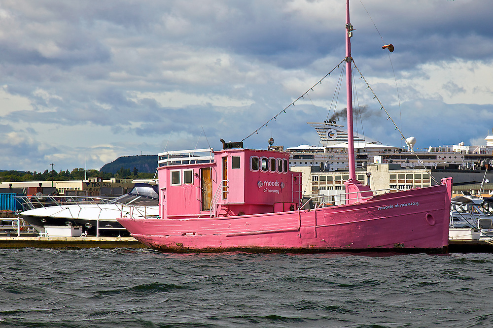 The brightly colored pink boat Moods of Norway in the harbor at Oslo, Norway