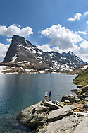 Two female hikers at the lake Geisspfadsee with the peaks of the Rothorn and the Schwarzhorn, Landschaftspark Binntal, Valais, Switzerland
