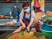 01 DECEMBER 2016 0 BANGKOK, THAILAND: A woman cuts up chillies in the traditional market on Lan Luang Road in Bangkok. The market is on the site of one of the first western style cinemas in Bangkok. The movie theatre closed years ago and is still empty but the market fills the streets around the theatre.     PHOTO BY JACK KURTZ
