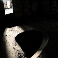 Sunlight shining into an old barn through a doorway onto a grain dip in the floor