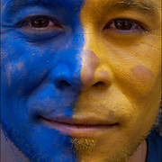 Close up portrait of face of male with half his painted face  blue and the half yellow.