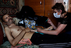 A nurse from the TB Hospital visits Ivan Korolink every day to give him his TB medicine and apply an IV for his diabetes.  Korolink's diabetes makes it difficult for him to travel to the hospital every day to retrieve his medicine.