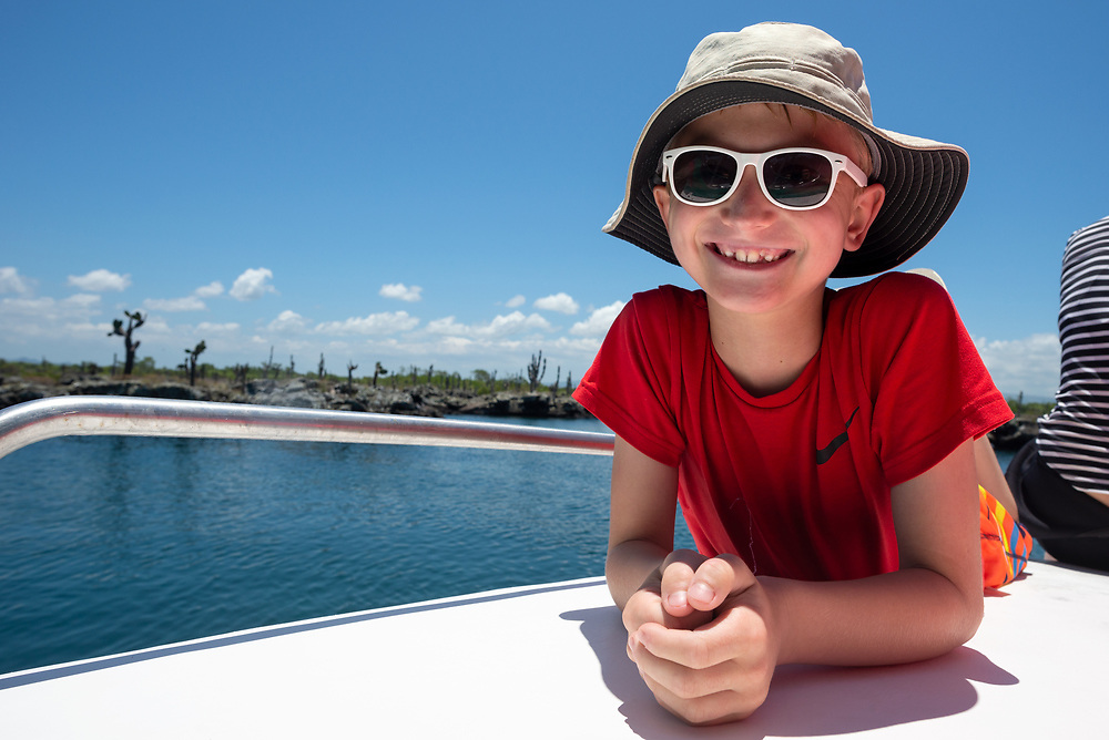 Smiling boy on the deck of a boat in the Galapagos Islands, Ecuador.