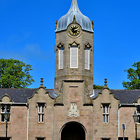 The Simpson Building at Gordon Schools in Huntly, Scotland <br /> The Simpson Building was named after its architect, Archibald Simpson.  It was funded by Elizabeth Brodie, the Duchess of Gordon, and constructed in 1839 to honor her husband, George Gordon, the 5th and last Duke of Gordon. It is the grand entrance to The Gordon Schools, a six-year secondary school founded by the duchess in the same year.  Beneath the clock tower is the Clan Gordon crest featuring a stag's head. On the other side of this arch is a tree-lined avenue leading to the Huntly Castle ruins.  This pathway provides a peaceful and lovely stroll.