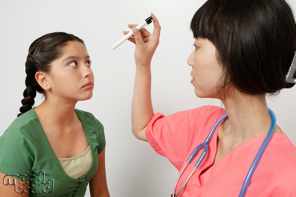 Doctor examining girl in hospital