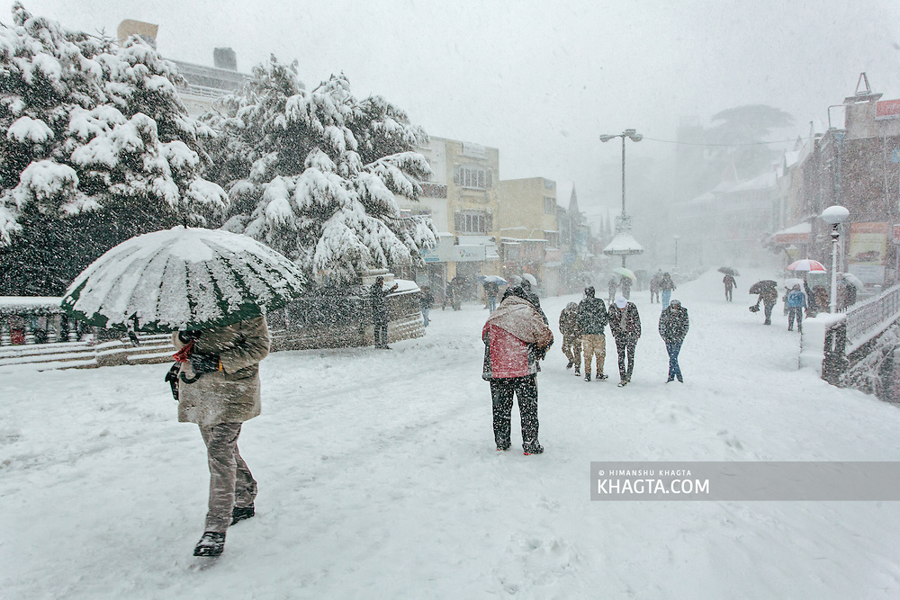People walking through a snow storm at the Scandal Point of Shimla
