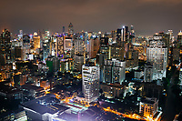 A cityscape of dense buildings in downtown Bangkok, Thailand at night.