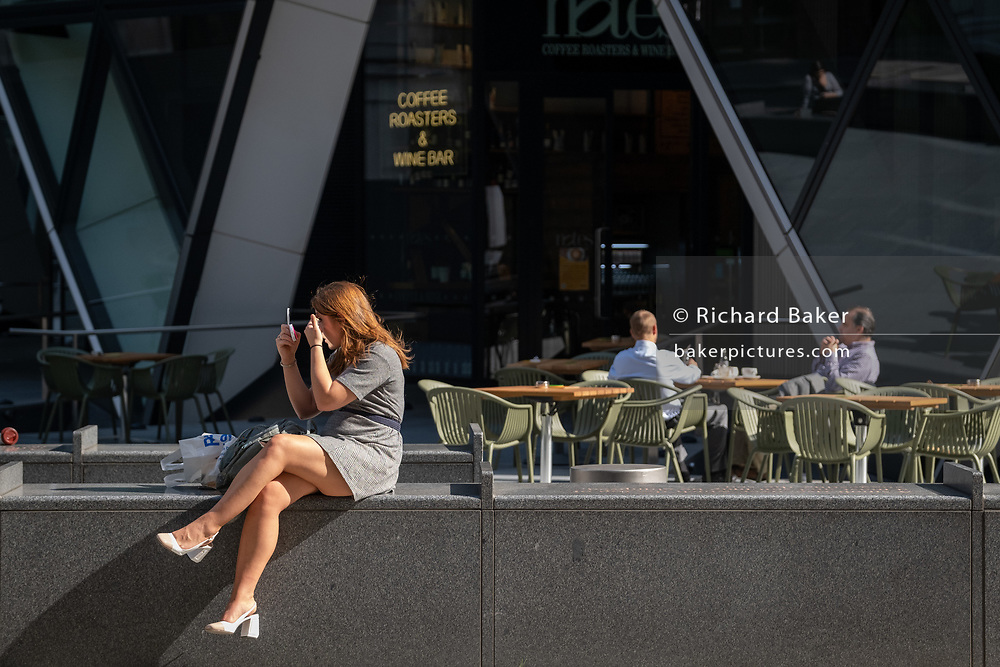 A woman applies make-up beneath the architecture of the Swiss re Building, aka the Gherkin, in the City of London during the Coronavirus pandemic, a time when office workers are still largely still working from home, on 16th September 2020, in London, England.