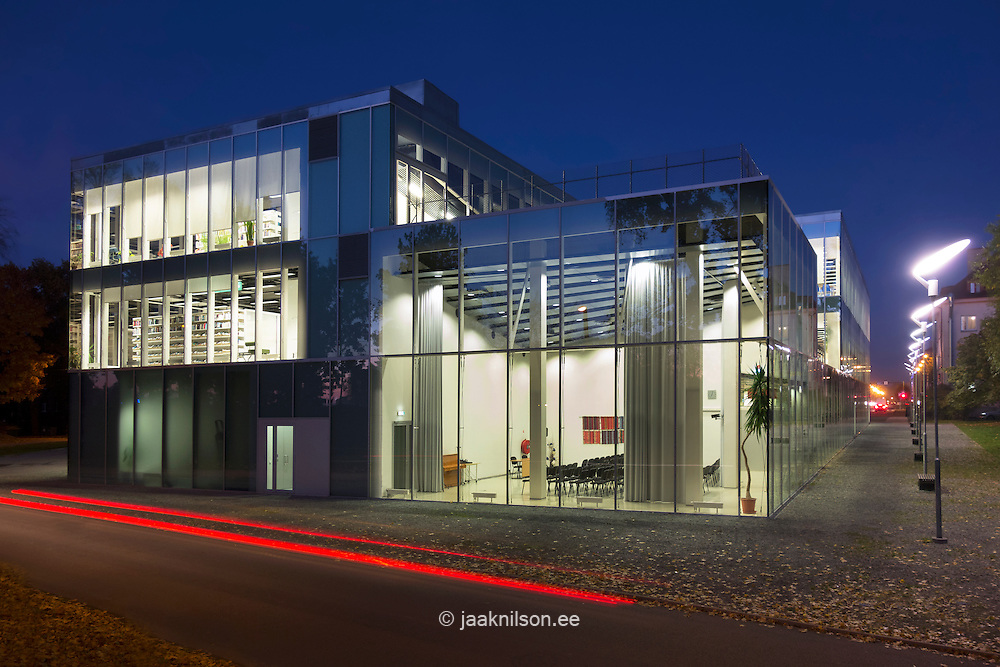 Exterior of Pärnu public library in Estonia. Glass wall. Car light trail, movement.