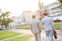 Rear view of businessmen walking at park on sunny day